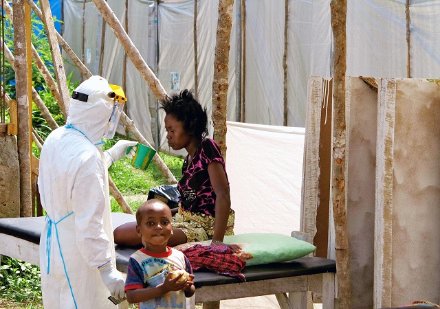A health worker, wearing head-to-toe protective gear, offers water to a woman with Ebola virus disease, at a treatment centre in  Kenema