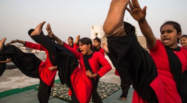 LUCKNOW, INDIA - MAY 17: Young women of the Red Brigade take part in a martial arts training session on the roof of a building on May 17, 2013 in Lucknow, India. The Red Brigade was formed in November 2010 to fight back against a growing number of sexual attacks on women in the Madiyav neighbourhood in the city of Lucknow, in the state of of Uttar Pradesh state, India. The group of young women wear distinctive red and black salwar kameez, and most  have been victims of sexual assault. They take direct action against predators with self defence learned in martial arts classes held for the group. The group work to empower its members and hope to be able to roll-out an education program for women. (Photo by Daniel Berehulak/Getty Images for Der Spiegel)