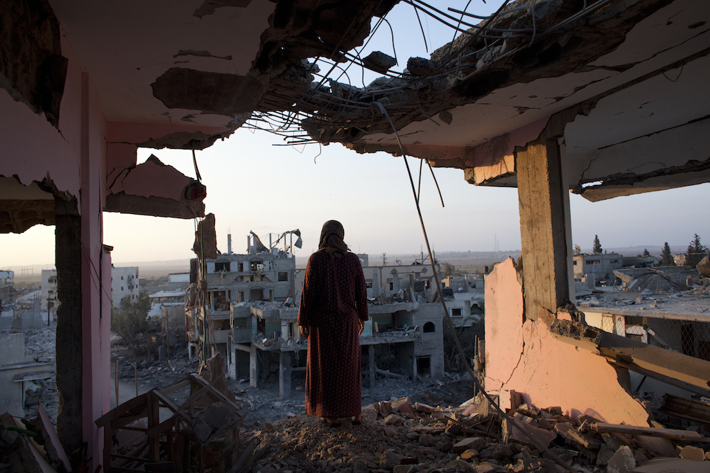 A Palestinian woman overlooks the destruction in Shujayea at dawn Aug. 8, 2014. On Friday the 72 hour cease fire came to an end without a longer term agreement . Rockets fired by Palestinian militants hit Israel and Israel resumed its air strikes .(Photo by Heidi Levine/For The National/Sipa Press).