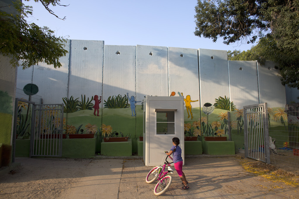 A young Israeli girl outside the kindergarden in Kibbutz Nahal Oz which has now been fortified by a series of cement  security walls to help ensure the children's safety ever since last summer's war between Israel and the Hamas-controlled Gaza Strip.The security wall has been painted to help the children feel more at ease .(Photo by Heidi Levine for The Globe and Mail).